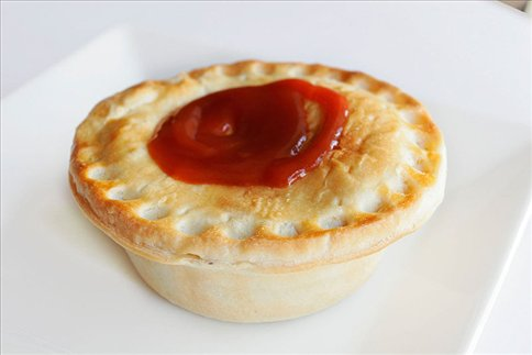 traditional aussie meat pie with ketchup (or tomato sauce, as they would say)