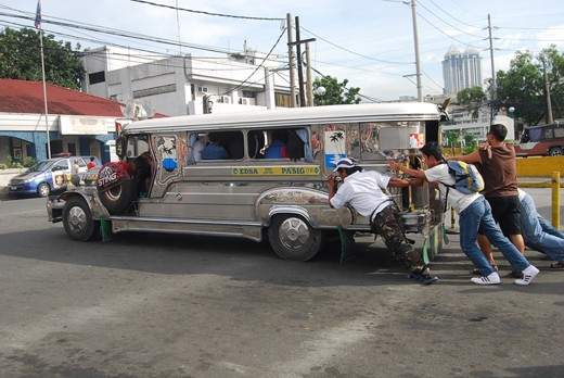 Engine failure led this jeepney to be given a jump start from the people near it