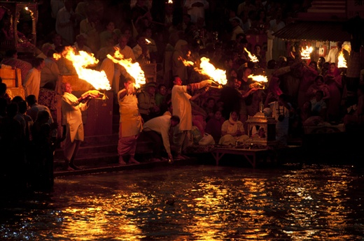 The temple priests waving large oil lamps during the Ganga Aarti