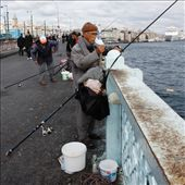 This fisherman has wrapped up warm for a long day holding his line. Accompanied by a deep bucket for his catch his aim is to fill it with migrating fish in the Bosphorus River.: by sarahg, Views[23]